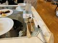 透明なテーブルに銀のカトラリー