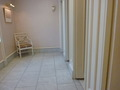 白い木目調のトイレドアーと休憩イス(本館17階レストラン階トイレ)