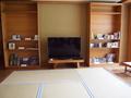 ラウンジの大型テレビと本・DVDの棚